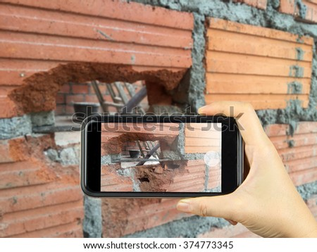 take photography with smart phone electric sockets installation in brick walls at house construction site - stock photo