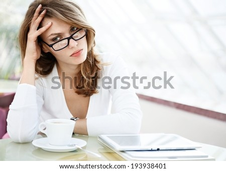 Take thought / photo of beautiful woman sitting in a coffee house