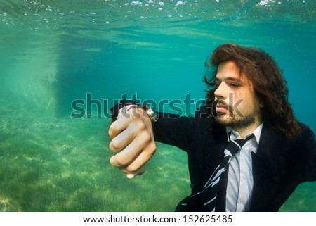 Take your business anywhere. Businessman Underwater watching time. Carpe Diem. - stock photo