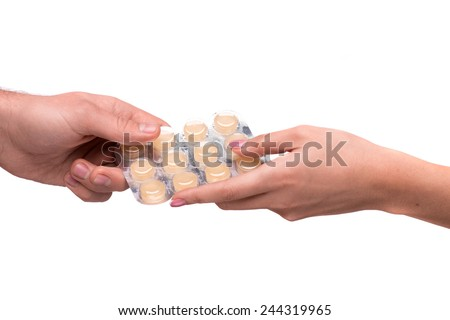 Take your pills. Cropped image of pack of pills passing between hands isolated on white - stock photo