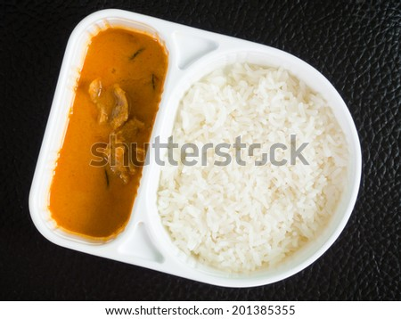 Takeaway rice and curry in a meal box. - stock photo