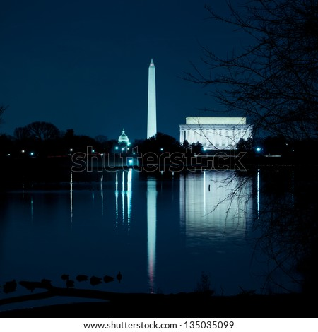 Taken from across the river, the Washington DC monuments reflecting in the Potomac River. - stock photo