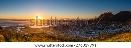 Taken from near the top of Signal Hill, Cape Town, I caught the beautiful moment the sun broke over the distant hills. This cropped panorama comprises of 9 images. - stock photo
