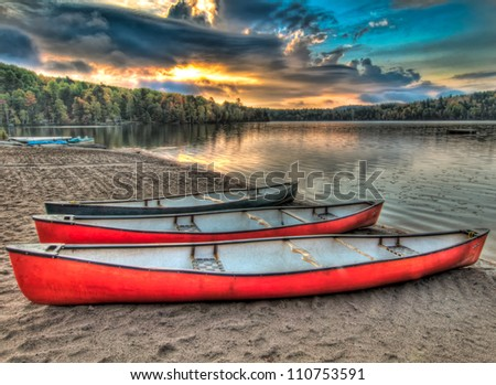 Taken in Northern Ontario Canada, these three colorful canoes are peacefully waiting as the sun rises through the clouds in the distance. - stock photo