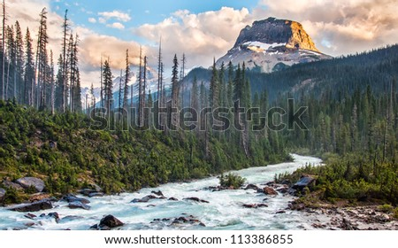 Taken in Yoho National park just as the setting sun lit the one side of this rockey peak. - stock photo