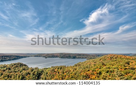 Taken near Algonquin park in Northern Ontario this lake stands out among the fall trees. - stock photo