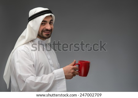 Taking a break from business meeting. Happy Arab man in headscarf holding a cup of tea isolated on grey background  - stock photo