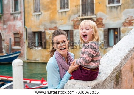 Taking a break is fun when you can sit along the water's edge and have fun together! Here, a mother and daughter are laughing with joy, being silly together, and enjoying themselves. - stock photo