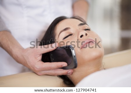 Taking a call while relaxing at a health and beauty spa - stock photo