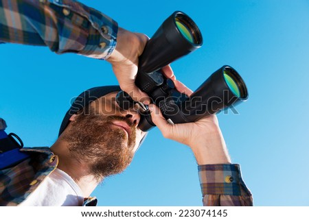 Taking a closer look. Long angle view of handsome young bearded man looking through binoculars away  - stock photo