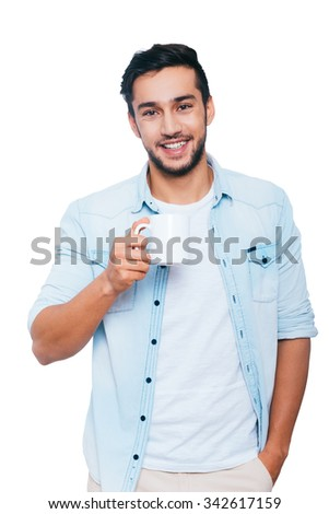 Taking a coffee break. Handsome young Indian man holding coffee cup and smiling while standing against white background - stock photo