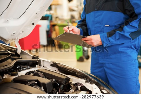 Taking a look under a hood. Close-up of man in uniform examining car and writing something in clipboard while standing in workshop