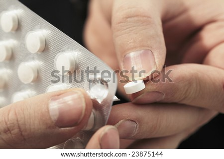 Taking a medicine pill out from a blister pack - stock photo