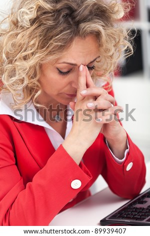Taking a moment in the office - woman with headache having deep thoughts - stock photo