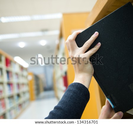 Taking book from book shelf in a library. - stock photo