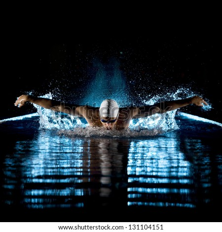 Taking breath swimming butterfly isolated black background - stock photo