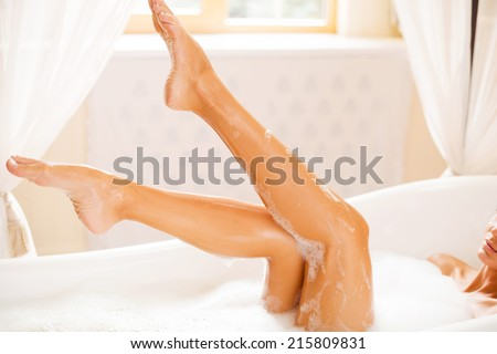 Taking care of her beautiful legs. Side view of beautiful young woman touching her leg while enjoying luxurious bath - stock photo