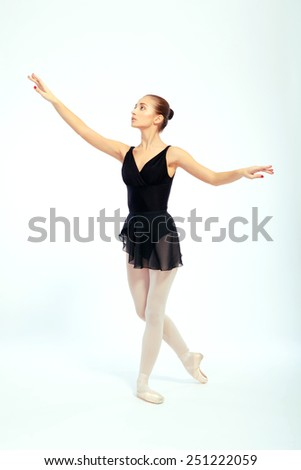 Taking dance to the next level. Full length portrait of beautiful ballet dancer in black ballet skirt while posing isolated on white background - stock photo