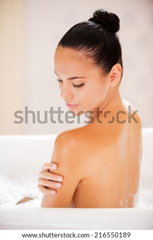 Taking good care of her skin. Rear view of attractive young woman touching her shoulder while enjoying bubble bath  - stock photo