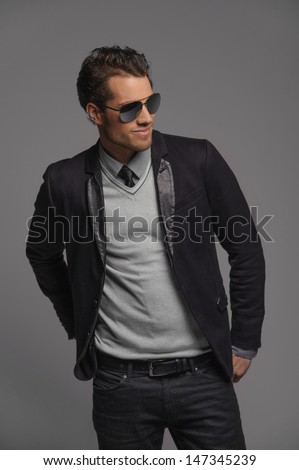 Taking it easy. Handsome young men posing with his hands in pockets and looking away while standing isolated on grey - stock photo