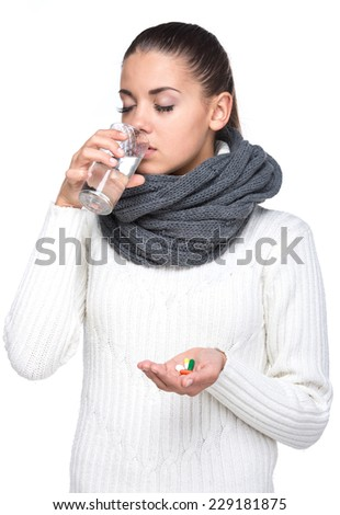 Taking medication. Young woman with glass of water taking pills, isolated on white. - stock photo