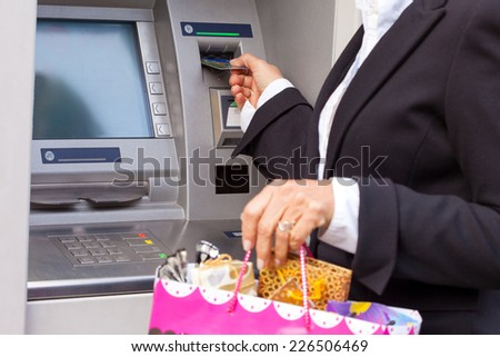 Taking money from ATM for shopping, selective focus - stock photo
