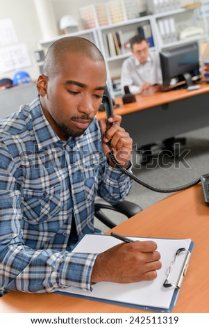 Taking notes during a phone call - stock photo