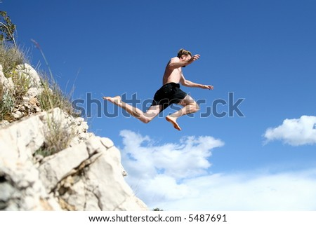Taking Off A young man jumps from a cliff into the sea!
