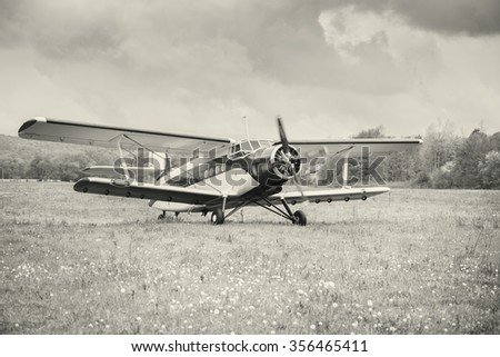 Taking off the old retro plane from the meadow. - stock photo