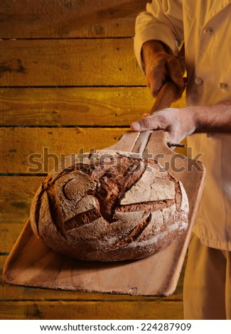 Taking out the bread from the oven. - stock photo