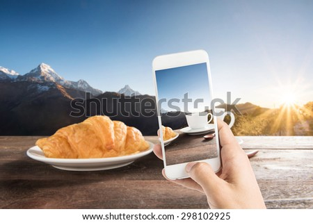 Taking photo of fresh baked croissants and coffee on a wooden table at mountain view. - stock photo