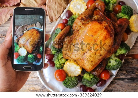 Taking photo of roasted turkey with vegetables for thanksgiving day - stock photo