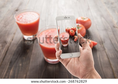 Taking photo of vegetable smoothie made of red ripe tomatoes on wooden table - stock photo