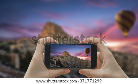 Taking photo on smart phone concept.Hot air balloon flying over spectacular Cappadocia. - stock photo