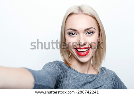 Taking picture. Smiling cheerful blond-haired woman doing selfie on isolated white background - stock photo