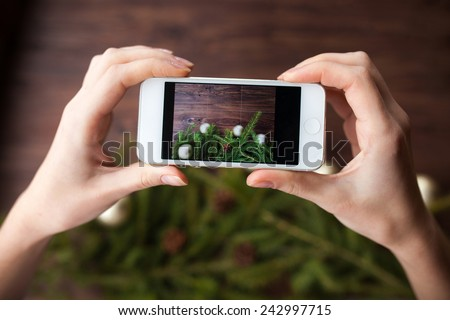 Taking picture with smartphone on brown wooden background