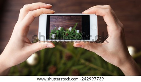 Taking picture with smartphone on brown wooden background - stock photo