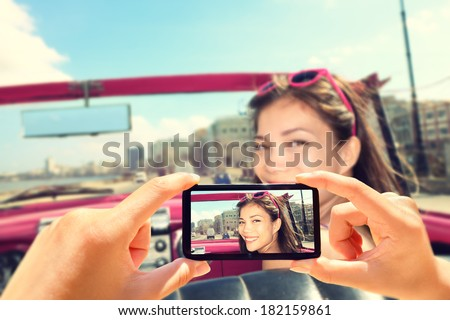 Taking pictures with smart phone of woman in car. Close up of camera phone showing photo of happy smiling woman driving in retro car. - stock photo