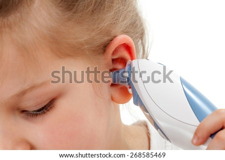 Taking temperature with ear thermometer - stock photo