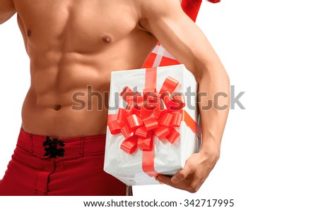 Taking this with me. Studio closeup shot of a ripped and toned young man holding Christmas gifts near his perfect abs - stock photo