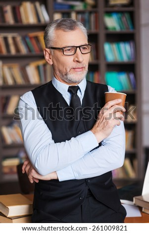 Taking time for a little break. Confident grey hair senior man in formalwear holding coffee cup and looking away while leaning at the table and with bookshelf in the background - stock photo