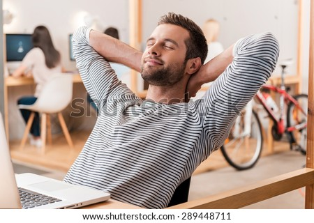 Taking time for a minute break. Cheerful young man holding hands behind head and keeping eyes closed while sitting at his working place with his colleagues working in the background  - stock photo