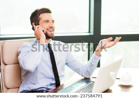 Taking time for coffee break. Handsome young man in shirt and tie holding coffee cup and looking at camera while sitting at his working place - stock photo