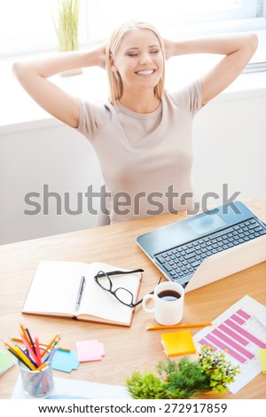 Taking time to have a rest. Top view of beautiful young holding hands behind head and smiling while sitting at her working place in office  - stock photo