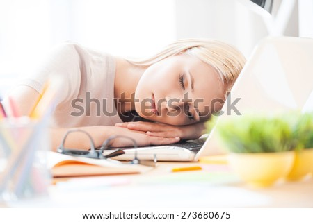 Taking time to have a rest. Top view of beautiful young woman looking at camera and smiling while sitting at her working place in office  - stock photo