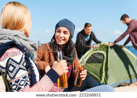 Taking time to have a rest. Two beautiful young women talking to each other and smiling while holding bottles with beer with two men setting up tent in the background  - stock photo
