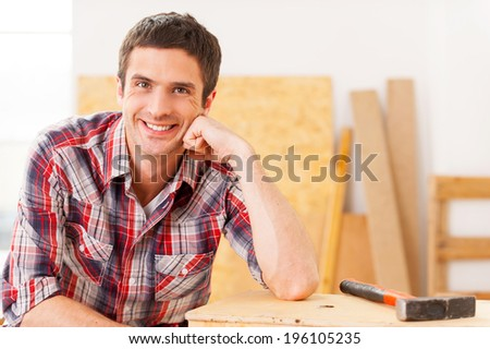Taking time to relax. Handsome young handyman smiling while sitting in workshop and leaning at the wooden deck  - stock photo