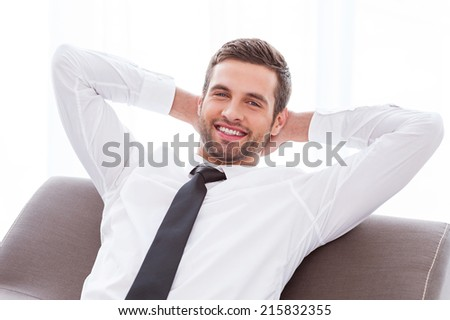 Taking time to relax. Happy young businessman in shirt and tie holding hands behind head and smiling while sitting at the chair