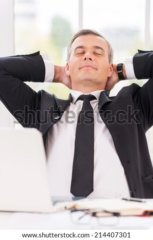 Taking time to relax. Relaxed mature man in formalwear holding hands behind head and keeping eyes closed while sitting at his working place - stock photo