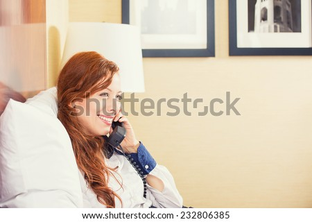 Taking time to talk with nearest. Beautiful young smiling businesswoman in white shirt and dress talking on phone while sitting on the bed in hotel room. Travel, communication, socializing concept  - stock photo